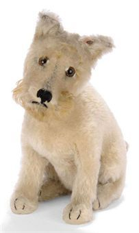 A STEIFF HEAD-TURNING RATTLER, (3325,2H), seated, cream mohair, brown tipped long mohair beard and brows, brown, black and white eyes, black stitching, inoperative squeaker, collar with two FF button and FF button with remains of red tag, 1930s --9½in. (24cm.) high (small bald spots to right cheek and slight wear)