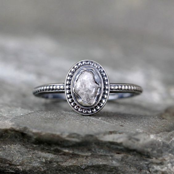 This vintage inspired ring features beaded detail surrounding a natural raw uncut rough diamond. The raw diamond is bezel set in this sterling silver ring. A oxidized patina accents the beaded detail in the metal work and the rustic texture of the raw diamond. The conflict free rough uncut diamond measures approximately 6 x 5 mm and weighs approximately 1 carat. The overall size of the top focal area of this ring is approximately 10 x 8.5 mm. The band measures approximately 1.5 mm in width…