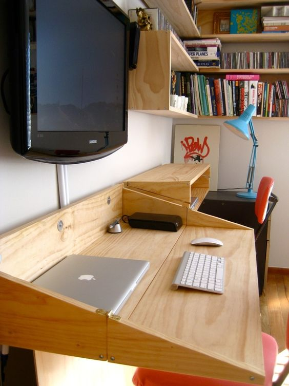 Name: Tim Grocott Location: Auckland, New Zealand Your Home Office Organization or Tech Tip: We needed a dual use space, this is our office as well as our TV room. So we wanted a workspace that would minimise when we just wanted to sit back and watch TV. When folded up, the desks resemble the shelves on the wall, and double in depth when unfolded. Also, the cables/modem etc. is all hidden behind the fake walls hanging on hinges from under the desk. The hiding of the cables has made the bigges...