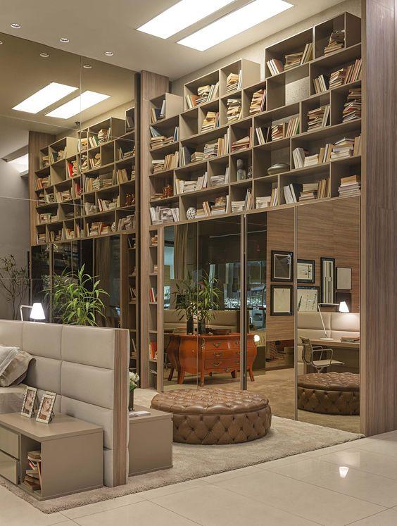 O grande armário ao fundo projetado por Walléria Teixeira sustenta grandes nichos e conta com uma escada vertical cromada que dá acesso às partes mais altas.