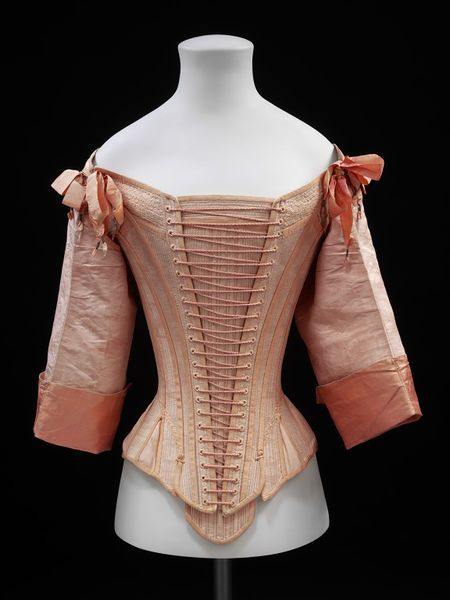 Salmon pink stays, 1660-1680 at V&A. Made out of ten pattern pieces, giving it a slightly more curvaceous shape than earlier stays and making the waist more round rather than oval. One layer of watered silk and one layer herringbone weave linen, possibly ticking, bound with silk grosgrain ribbon. Laced in front over a boned, T-shaped stomacher.