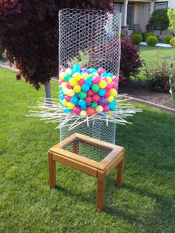 """""""Backyard Ker-Plunk"""". I made this DIY Ker-Plunk game by upcycling an old end table I found on craigslist. We wrapped some chicken wire around the top, stapled it in place to secure, and voila! Homemade Ker-plunk! We got the wooden dowels at Home Depot and I found the ball pit balls on craigslist. But of course, you can get them at Walmart or Toys R Us. It's a ton of fun!"""