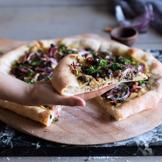A vegan hummus pizza, made from scratch, with detailed instructions. Cooked hummus over the perfect artisanal crust is intensely delicious. #bread #hummus #mushrooms