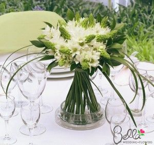 Bella's wedding in a box star of bethlehem bouquets and centerpieces are designed with subtle accents of looped lily grass and fresh ruscus leaves. The white star of bethlehem wedding arrangements are secured with a coordinating white ribbon.