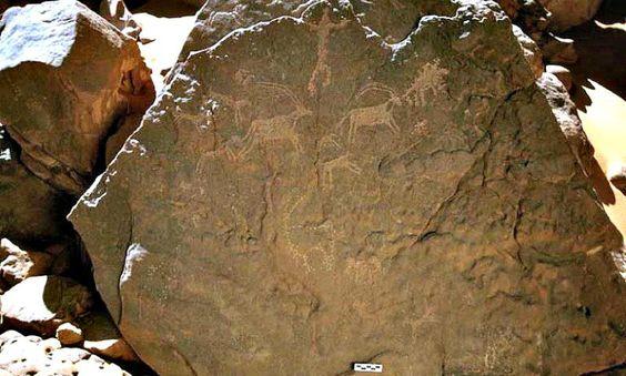 Roca de Gilf Kebir en cuyos grabados se pueden ver unos perros atacando a tres oryx (antílopes) bajo un hombre que observa la escena con los brazos abiertos. (Fotografía: La Gran Época/TARA)