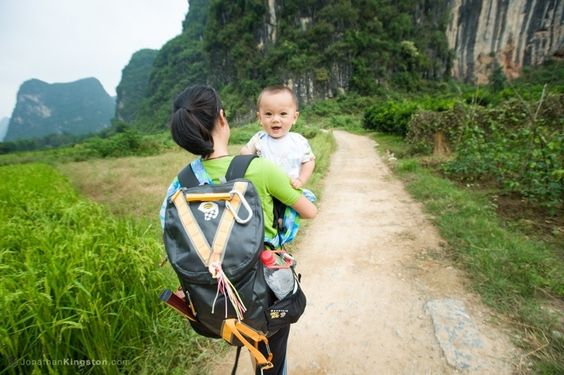 Chinese rock climber and super mom carrying her boy back from a day at the crag near Yangshuo, China.