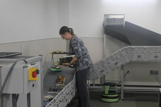 """Behind the scenes at the newly renovated Ames Public Library, a new """"automated materials handling system"""" is connected to an outside dropbox. Library materials are scanned in as they move down the conveyor belt and are sorted into bins depending on what section they belong to. Photo by Melissa Erickson/Ames Tribune"""