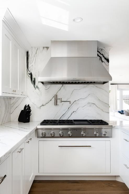 A Gorgeous Black And White Marble Slab Backsplash Holds A Stainless Steel Range Hood Black And White Marble Black Marble Countertops Black And White Backsplash