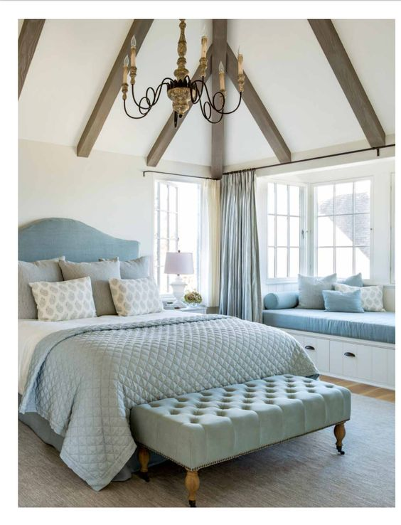 Beautiful tranquil and timeless romantic feminine bedroom in French inspired modern farmhouse in California by Giannetti Home. Light blue upholstered headboard and bedding, tufted ottoman, window seat, Aidan Gray chandelier, rustic wood beams, vaulted ceiling, and European style.