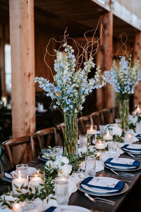 Simple reception centerpieces with a big impact. Tall blue delphinium arrangements with curly willow branches, greenery runner, candles and small accent designs. Floral: Wildflowers LLC Photo: Eden Ingle Photography