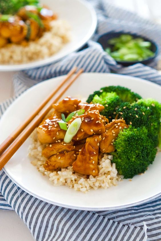 These delicious Skinny Honey Teriyaki Chicken Rice Bowls are a super quick dinner! Tender chicken is sauteed until juicy and simmered in a homemade, healthy teriyaki sauce. Served with fresh veggies and rice, you will forget all about takeout!: