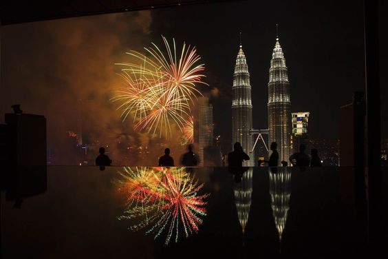 Fireworks explode near Malaysia's landmark Petronas Twin Towers which are reflected in a pool during New Year celebrations in Kuala Lumpur