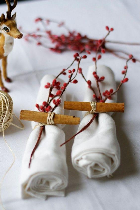 déco table Noël rouge et blanc - des serviettes pliées en rouleau et décorées de baies rouges givrées et bâtons de cannelle