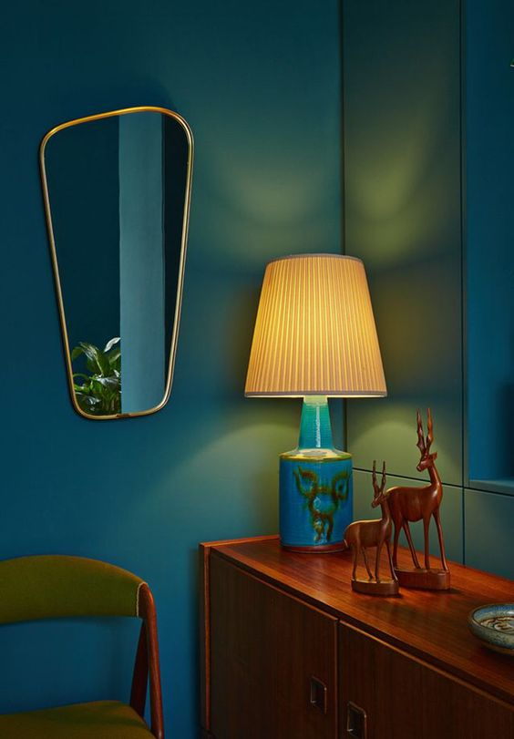 A few choice accessories such as this mirror and safari ornament can make a dark room have a mid-century feel