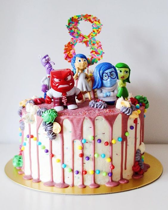 By far the most colorful cake I've ever done. This Inside Out themed cake has 5 rainbow layers of vanilla sponge, is fully decked in vanilla buttercream, dripping with pink tinted white chocolate ganache, and complete with cake topper characters.