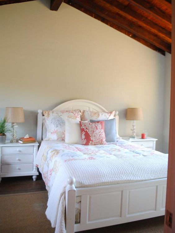 As seen on HGTV's Vacation House for Free...an open and airy space, the master bedroom with en suite bath gives visitors a welcomed space to relax after a day on the beach. White furnishings and light textiles contrast against the dark ceiling beams, giving this space a bright and spacious cottage look.