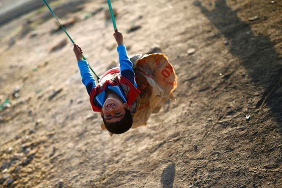 Best pictures of the week: October 25, 2014; A Kurdish refugee child from the Syrian town of Kobani plays on a swing in Suruc, Sanliurfa province, Turkey.