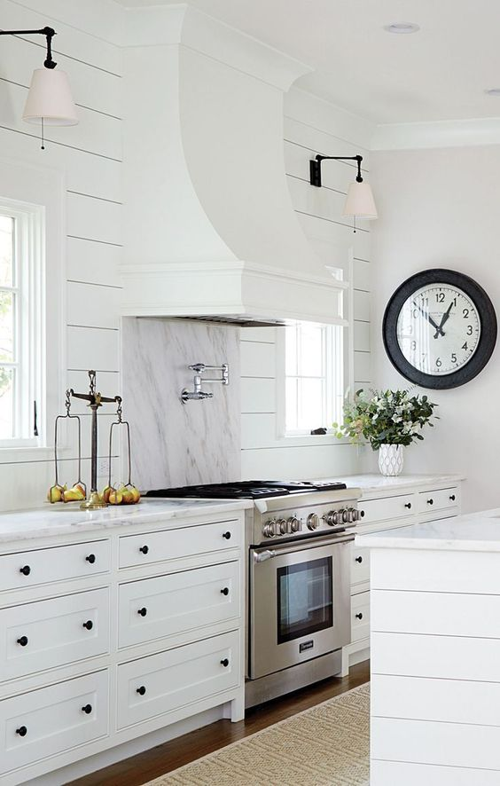 White modern farmhouse kitchen with shiplap, a sculptural range hood, and an oversized clock. #modernfarmhouse #farmhousekitchen #marblebacksplash #shiplapwalls