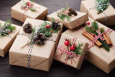 Heap of gift or present box wrapped in kraft paper with christmas decoration on rustic wooden background.