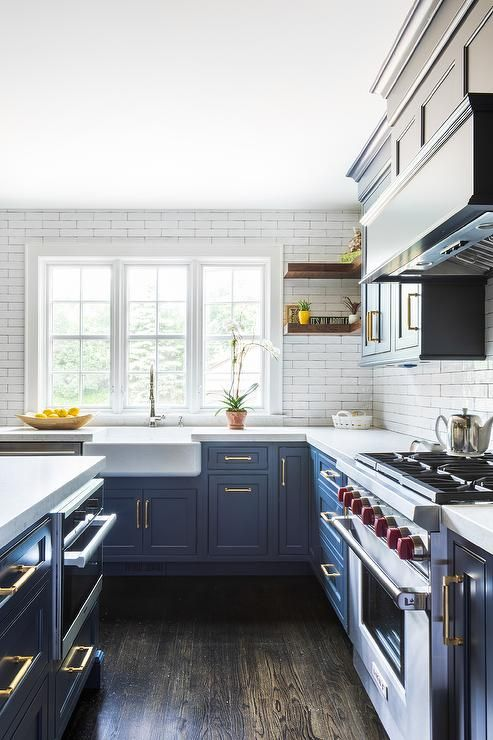 White Kitchen Cabinets With White Quartz Countertops Farm sink in a contemporary kitchen boasting blue cabinets, white