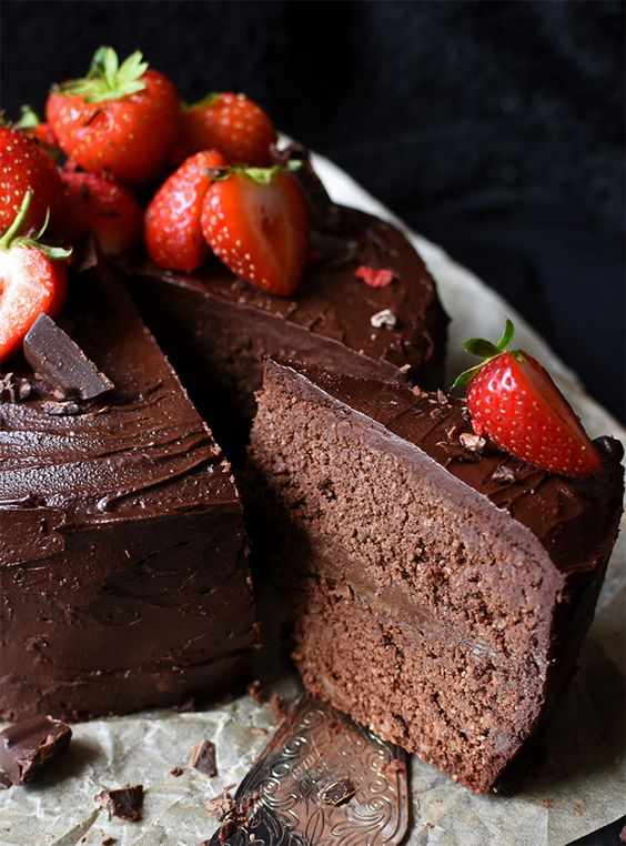 A rich raw chocolate ganache cake with caramel and avocado buttercream filling, that's perfect served with raspberries, strawberries and whipped coconut cream.