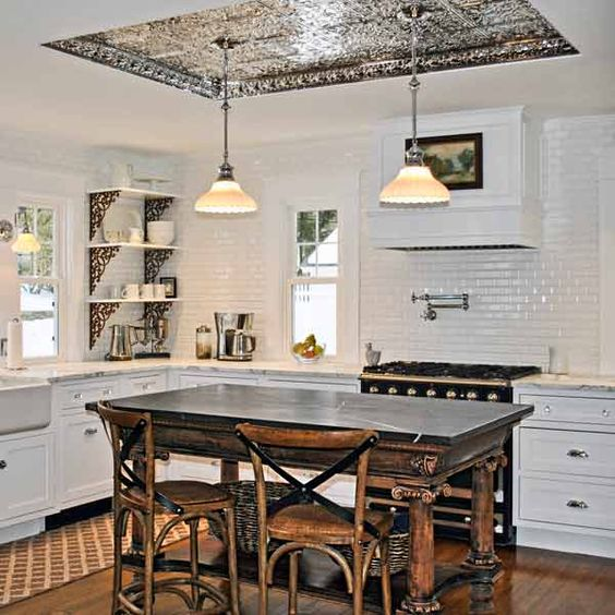 Inspired by an antiques store they like to frequent, these homeowners moved a beam in the kitchen to put in a recessed tin ceiling with  pendant light fixtures.