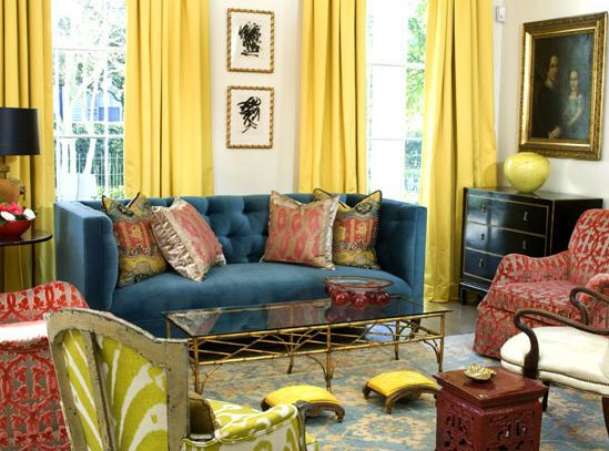 living rooms - bright yellow silk drapes. blue velvet tufted sofa red gray chairs lime green chair brass coffee table red garden stool black vintage chest gold blue damask rug LOVE MMR Interiors