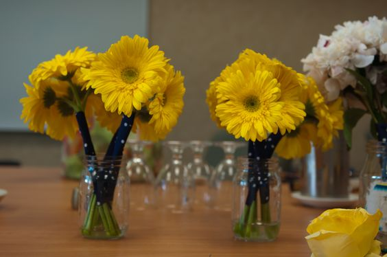 Gerbera daisies wrapped with navy and white polka dot fabric.