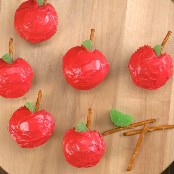 Cupcakes decorated like apples, pretzel stick stems and jelly candy leaves