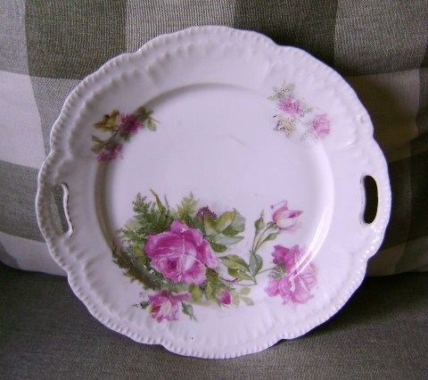 A very old, but beautiful handled plate with roses.