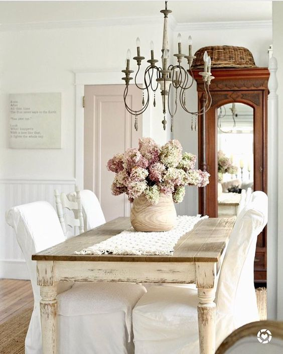 Shabby chic dining room with blush flowers, French chandelier, and slipcovered chairs. #shabbychic #diningroom #hydrangea