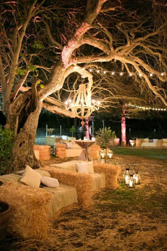 Garten Party mit Sessel aus Stroh, Laternen am Boden und Kronleuchter hängend vom Baum