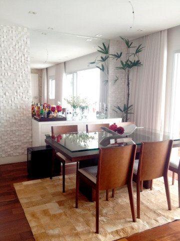 Esta sala de jantar conta com buffet, adega e espelho. O tapete dá o toque de aconchego. Projeto de Adriana Victorelli.