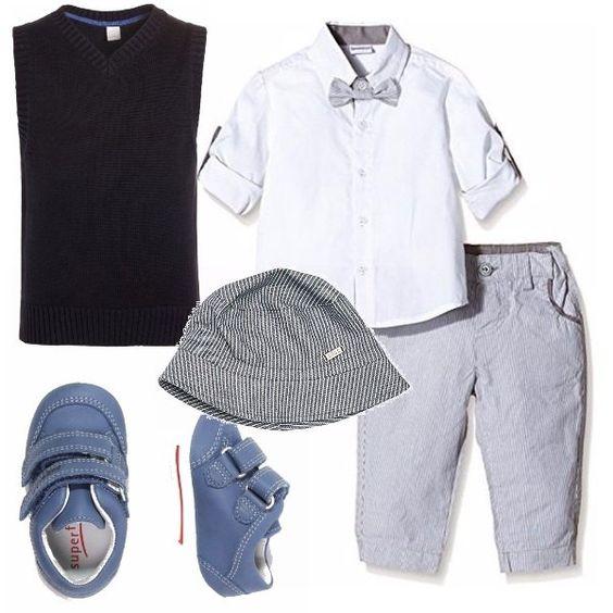 Completo formato da pantalone millerighe bianco e grigio come il papillon della camicia che è bianca e si possono arrotolare e fissare le maniche se è caldo. Se è fresco, mettiamo il gilet blu. Il cappellino è a righe bianche e blu e le scarpe sono celesti con velcro.