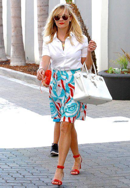 Fashion-Looks: Von Kopf bis Fuß top gestylt: Auf den Straßen von Beverly Hills leuchtet Reese Witherspoon in einem perfekt aufeinander abgestimmten Outfit . Mit ihrer weißen Bluse und den roten Sandaletten greift sie gekonnt die Farben ihres bunten Rocks auf.
