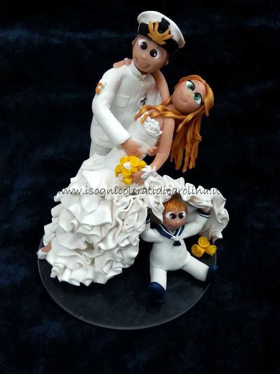 Romantico cake topper nunziale. Sposo della marina militare che tiene un caschè alla sua bellissima sposa. Il loro bimbo nascosto tra i vestiti della mamma. Realizzato a mano con pasta sintetica. Base in plexiglass.