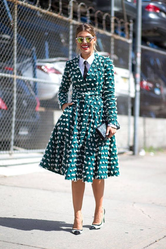 A New York Fashion Week show-goer rocking a green flared coat with all-over embroidery from #HMTrend. Photo by Diego Zuko for @harpersbazaar. #HMOOTD