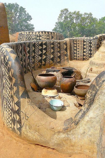 Burkina Faso - at the base of a hill overlooking the surrounding sun-drenched West African savannah lies an extraordinary village, a circular 1.2 hectare complex of intricately embellished earthen architecture.: