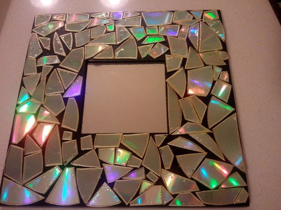 Break old CDs to create a mosaic frame. Love the way it reflects light