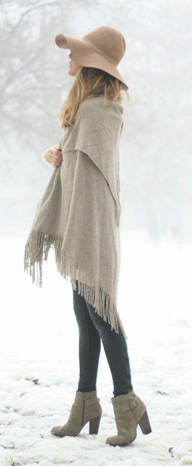woman standing in snow wearing a dark cream wool floppy hat with a grey shawl, black leggings and grey booties