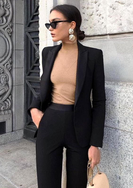 Mujer usando un traje negro, aretes dorados grandes. Muy de moda