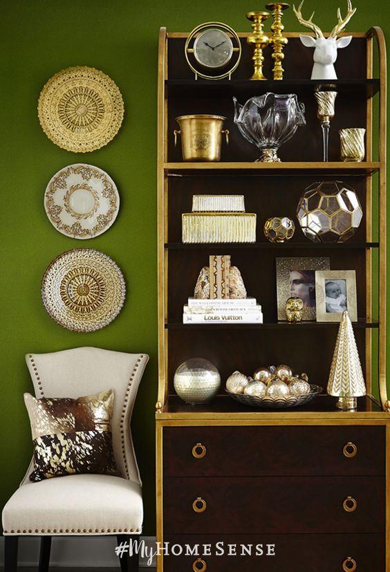 stylist tip: a cohesive colour theme gives a shelving display sophisticated style. Here, the white and gold accessories pop against the dark wood bookshelf and moss green walls.