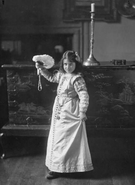 Nine year old future Queen Elizabeth, Lady Elizabeth Bowes-Lyon, posing with fan during a dancing lesson at the ancestral Glamis Castle. Forfarshire, Scotland, 1909.