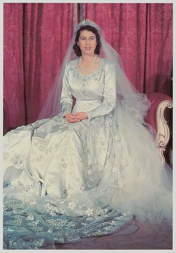 Queen Elizabeth II, 1947.  Princess Elizabeth wore a full length silk gown made of ivory duchesse satin, designed by Norman Hartnell. The dress, with a 15-foot train that was attached at the shoulders, was embroidered at the neckline, as well as along the sleeve edges, the front bodice and throughout the skirt and train with garlands of orange blossoms, jasmine, the white rose of York, and ears of wheat. Ten thousand seed pearls were used for the embroidery. It is said that women from all…