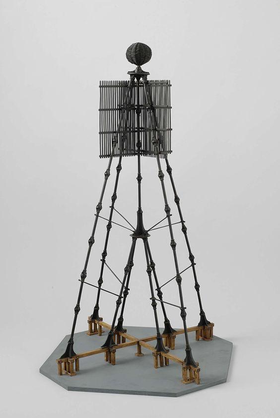Rijkswerf Willemsoord | Model van een kustkaap, Rijkswerf Willemsoord, c. 1850 - c. 1855 | Houten model van een ijzeren, zwart geverfd en op een grondplank. Het raamwerk bestaat uit ronde ijzeren staven met platte schijven aan de uiteinden, die aan elkaar gebout zijn; het geheel wordt verstevigd met trekstangen. Het heeft vier buiten- en vier binnenpoten, die op een houten kruis staan dat ter plekke van de poten onderheid is. Bovenaan twee elkaar kruisende schermen van lamellen; geheel…