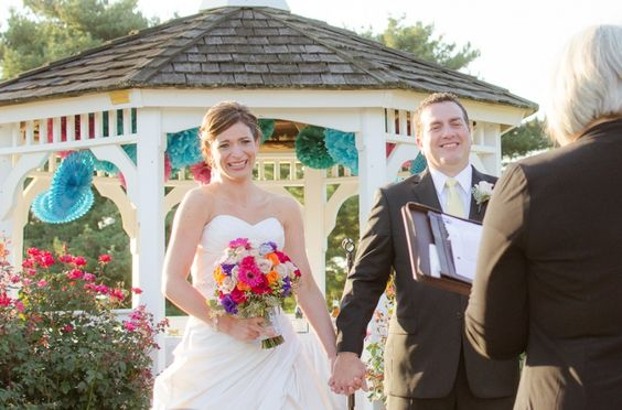 Love the paper pinwheels and pom pom decorations. Great DIY decor for the ceremony arch! Melinda Snyder Photography.