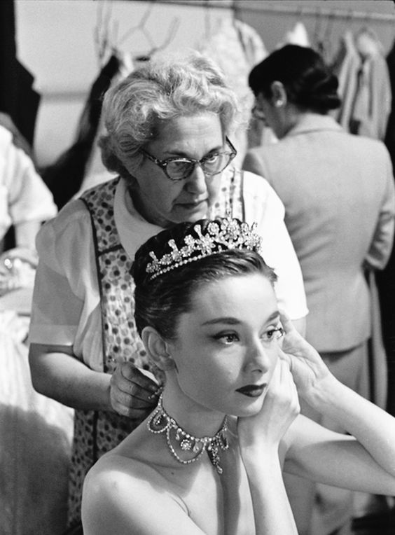 Audrey Hepburn (with Edith Head in the background) puts on her tiara and necklace while on the set of Roman Holiday, 1952.