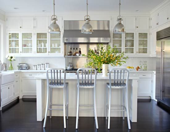 All-White Kitchen with Black Floor: White scullery-type cabinets mingle with glossy white subway tiles, marble countertops, and stainless steel appliances to create a pristine appearance in this light and airy room. Below, an oak floor stained ebony creates a dramatic contrast. | traditional home #kitchen #white kitchen #traditional kitchen