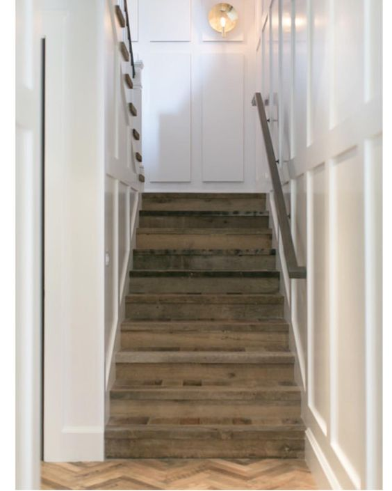 Vintage wood meets pristine white millwork... We think it's a match made in heaven.  #BWD #stairwell #customhome #vintagehardwood #millwork #paneling @arteriorshome @legacycdm #cynthiachilds #herringbonefloor
