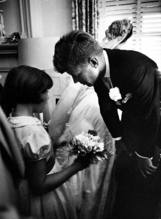 Flower girl Janet Auchincloss, half sister of bride, talks to John Kennedy while bride looks out window at guests waiting to go through receiving line.